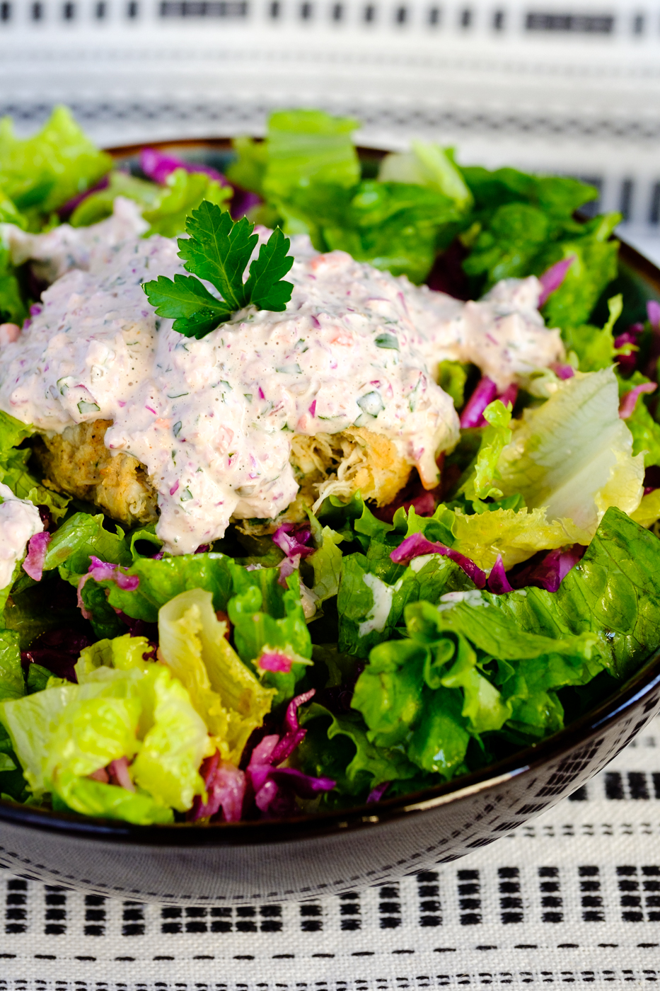 Lectin-free crab cakes in a bowl of salad with homemade remoulade